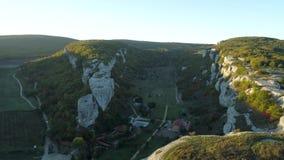 Красивый сценарный ландшафт горы с осенними холмами, пасмурным голубым небом и светом восходящего солнца на мглистом горизонте сток-видео