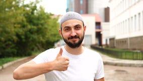 Красивый счастливый бородатый мусульманский большой палец руки показа человека вверх на камере акции видеоматериалы