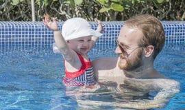 Красивый счастливый выразительный белокурый малыш девушки в бассейне с ее отцом Стоковая Фотография
