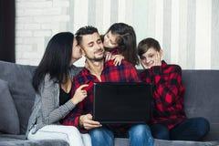 Красивый счастливый портрет семьи дома сидя совместно на софе стоковые фотографии rf