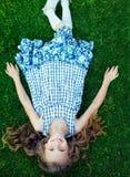 Красивый счастливый ребенк девушки лежа в траве Стоковое фото RF