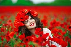 Красивый счастливый усмехаясь предназначенный для подростков портрет девушки с красными цветками на h Стоковые Фото
