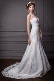 Красивый сладостный нежный groom девушки в платье свадьбы с венком и цветками в ее волосах в студии Стоковая Фотография RF