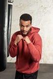 Красивый темнокожий боксер в костюме спорта практикует крюки и дует перед грушами Стоковые Изображения