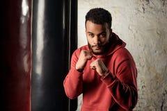 Красивый темнокожий боксер в носке спорта практикует крюки и дует перед грушами Стоковая Фотография