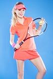Красивый теннисист девушки с ракеткой на голубой предпосылке Стоковые Изображения
