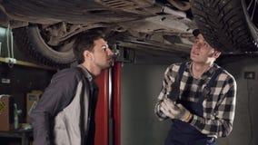 Красивый техник ремонта автомобилей показывая к его maleclient основные проблемы с автомобилем сток-видео
