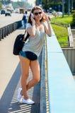 Красивый тонкий стильный студент девушки стоит на мосте автомобиля и Стоковое Изображение RF