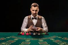 Красивый торговец шаркая пакет карт и обломоки играя на зеленой таблице стоковые изображения