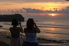 Красивый тропический заход солнца над океаном, Бали, Индонезией 2 женщины делая фото, редкий взгляд Стоковые Изображения RF