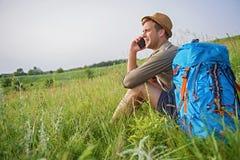 Красивый турист используя телефон в луге Стоковая Фотография RF