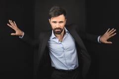 Красивый уверенно бизнесмен представляя в черном костюме Стоковые Фотографии RF