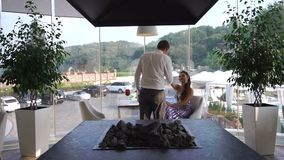 Красивый уверенно человек в костюме приходит к его очаровательной даме, целует ее руку и сидит на таблице романтично видеоматериал