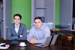 Красивый умный бизнесмен 2 или работники сидя на острословии таблицы Стоковое Фото