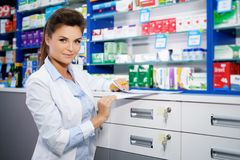 Красивый усмехаясь аптекарь молодой женщины делая его работа в фармации стоковые фотографии rf