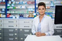 Красивый усмехаясь аптекарь молодой женщины делая его работа в фармации стоковое фото rf