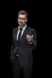 Красивый усмехаясь бизнесмен в черном костюме представляя что-то стоковая фотография