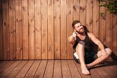 Красивый усмехаясь бородатый человек сидя и указывая палец на вас Стоковые Изображения RF