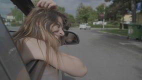 Красивый усмехаясь девочка-подросток идя на отключение полагаясь вне автомобиль окна выражая потеху и счастье свободы - сток-видео