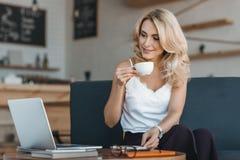 красивый усмехаясь кофе коммерсантки выпивая и работа с компьтер-книжкой Стоковые Изображения