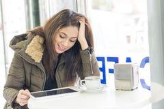 Красивый усмехаясь планшет компьтер-книжки женщины в кофейне стоковые фото