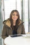 Красивый усмехаясь планшет компьтер-книжки женщины в кофейне стоковая фотография
