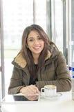 Красивый усмехаясь планшет компьтер-книжки женщины в кофейне стоковые фотографии rf
