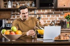 красивый усмехаясь сок человека лить пока использующ ноутбук стоковые изображения