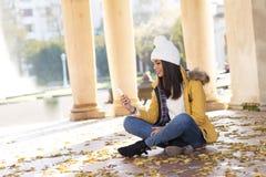 Красивый усмехаясь телефон womanwith сидя на листьях стоковая фотография