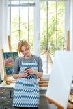 Красивый усмехаясь художник девушки представляя на камере окно на предпосылке белизна пятна краски маски принципиальной схемы чер Стоковое фото RF