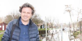 Красивый усмехаясь человек смотря камеру около берега озера реки стоковое изображение