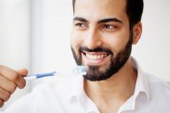Красивый усмехаясь человек чистя здоровые белые зубы щеткой с щеткой H стоковое фото rf