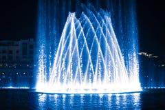 Красивый фонтан на ноче загоренной с голубым светом стоковое фото rf