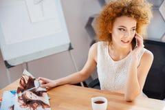 Красивый фотограф женщины говоря на мобильном телефоне в офисе Стоковые Изображения