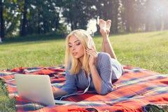 Красивый фрилансер девушки слушает к музыке на траве Стоковая Фотография RF