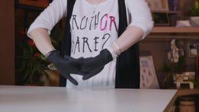 Красивый флорист вручает перчатки девушки нося Стоковое Фото