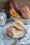 Красивый хлебец белого хлеба пшеницы на плите на linen крае разнообразие хлебов в корзине на заднем плане Стоковое Изображение RF