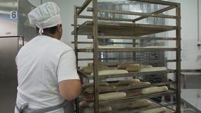 Красивый хлебопек в равномерных багетах прогулки и держать с хлебом shelves на предпосылке на хлебопекарне производства видеоматериал