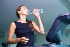 Красивый ход и питьевая вода девушки фитнеса на третбане на спортзале стоковое изображение rf
