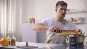 Красивый холостяк подготавливая томатный соус, наслаждаясь процессом варить, хобби акции видеоматериалы
