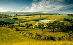 Красивый холмистый ландшафт с озером и голубым облачным небом Стоковая Фотография