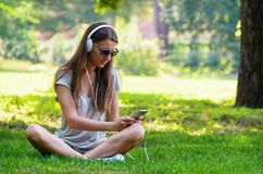Красивый худенький стильный студент девушки сидя на зеленых gras Стоковые Изображения RF