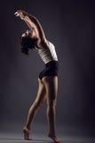 Красивый худенький спортсмен девушки танцуя barefoot под прожекторами студии нося высокие трусы талии и белую верхнюю часть Стоковое Изображение