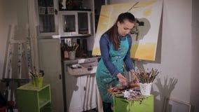 Красивый художник девушки сжимает вне трубку краски на палитре Студия искусства акции видеоматериалы