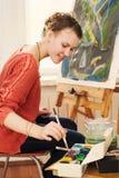 Красивый художник женщины рисуя ее изображение Стоковое Изображение RF