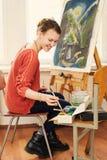Красивый художник женщины рисуя ее изображение Стоковое Фото