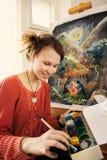 Красивый художник женщины рисуя ее изображение Стоковая Фотография RF