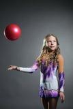 Красивый художнический гимнаст бросает шарик в студии Стоковая Фотография RF