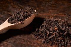 Красивый чай в деревянной ложке на черной предпосылке изолировано стоковые фотографии rf