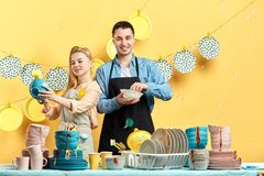 Красивый человек брюнета и его блюда девушки очищая в кухне стоковые изображения rf